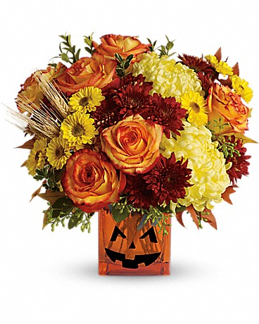 Teleflora's Halloween Glow Bouquet in a vase with a jack-o-lantern face
