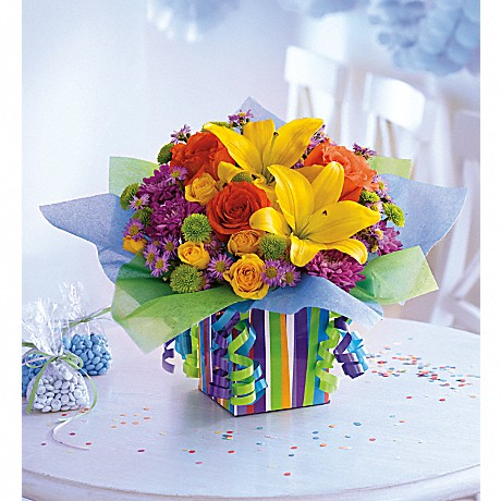 Teleflora's Rainbow Presentbouquet in Teleflora's exclusive keepsake gift box with streamers and tissue paper.